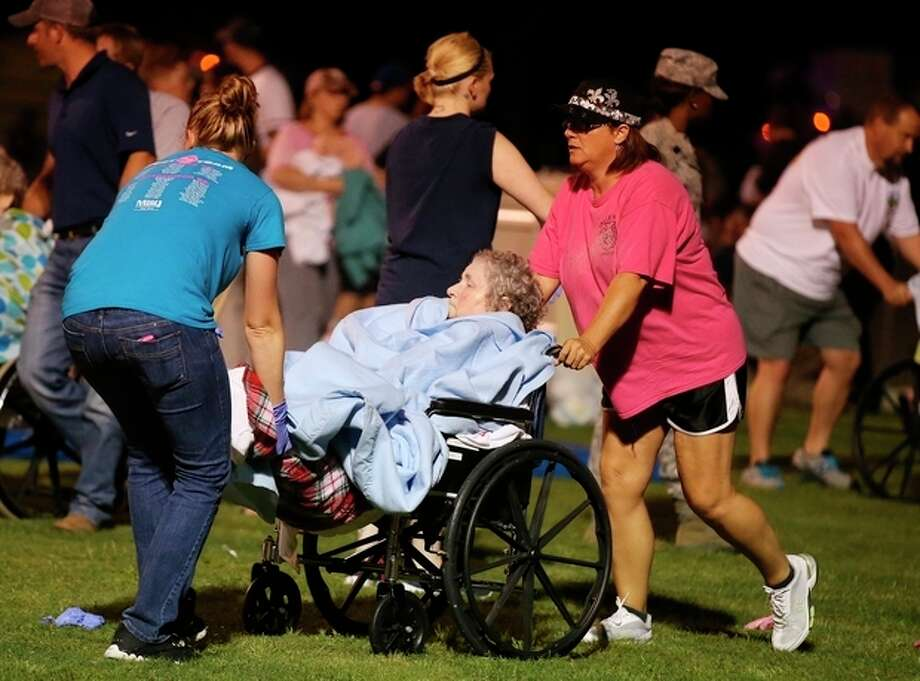 An elderly person is assisted at a staging area at a local school stadium following an explosion at a fertilizer plant Wednesday, April 17, 2013, in West, Texas. An explosion at a fertilizer plant near Waco caused numerous injuries and sent flames shooting high into the night sky on Wednesday. (AP Photo/ Waco Tribune Herald, Rod Aydelotte) / Waco Tribune Herald