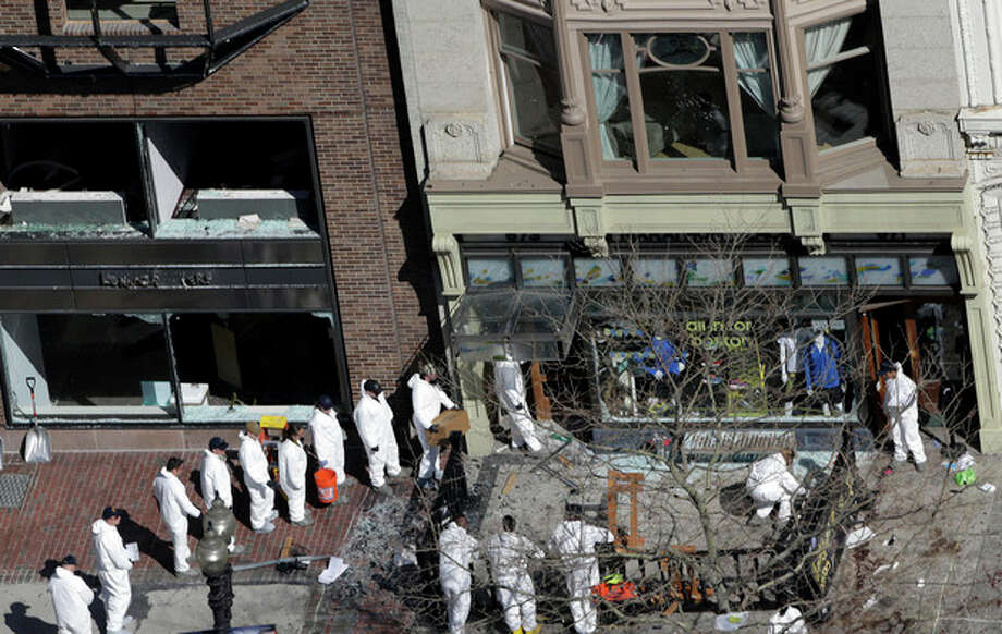 A line of investigators is form as they enter a building adjacent to one of the blast sites near the Boston Marathon finish line, Thursday, April 18, 2013, in Boston. Boston remained under a heavy security presence, with scores of National Guard troops gathering among armored Humvees in the Boston Common. (AP Photo/Julio Cortez) / AP