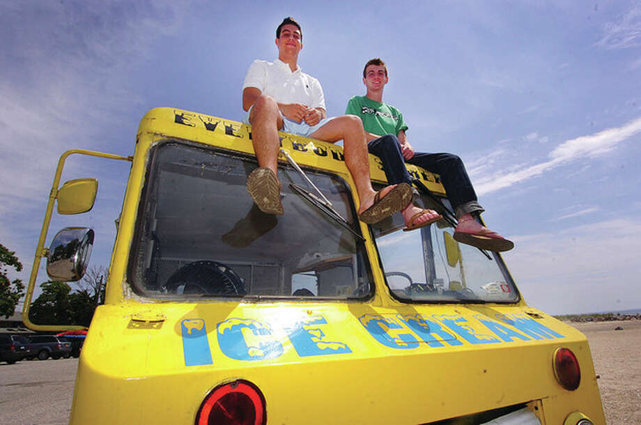 "Hour photo / Alex von KleydorffFrom left, Jon Camche and Rick Snyder perch atop their ""Everybody Scream! Ice Cream"" truck in Westport. The two teenage friends pooled their resources and started a summer business. / 2012 The Hour Newspapers"