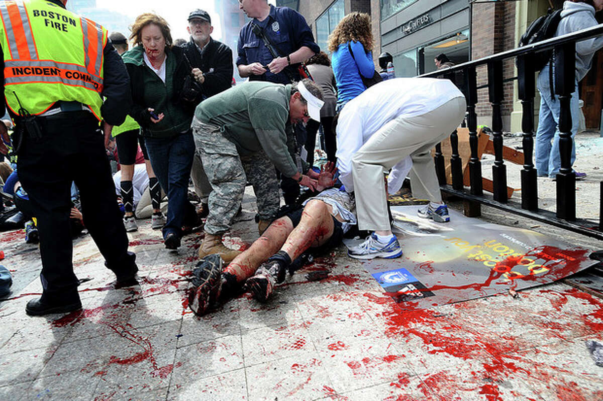 AP Photo/MetroWest Daily News, Ken McGagh, File In this April 15, photo, an injured person is helped on the sidewalk near the Boston Marathon finish line following an explosion in Boston.