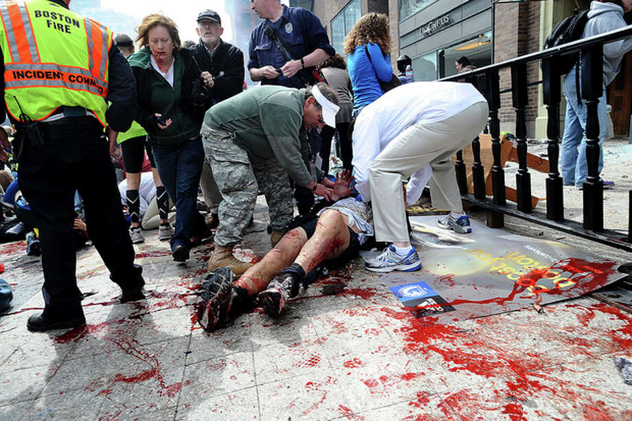 AP Photo/MetroWest Daily News, Ken McGagh, FileIn this April 15, photo, an injured person is helped on the sidewalk near the Boston Marathon finish line following an explosion in Boston. / MetroWest Daily News