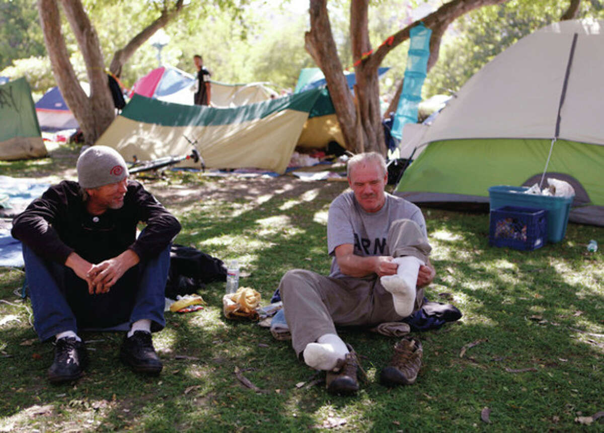 Terry, right, puts on his socks and shoes as he talks with George at Lincoln Park across from the Capitol in Denver, Colo., on Thursday, Oct. 13, 2011. Colorado Gov. John Hickenlooper said on Thursday that Wall Street protesters near the state Capitol can demonstrate during the day but must tear down their tent camp that is seen beyond the bell. (AP Photo/Ed Andrieski)