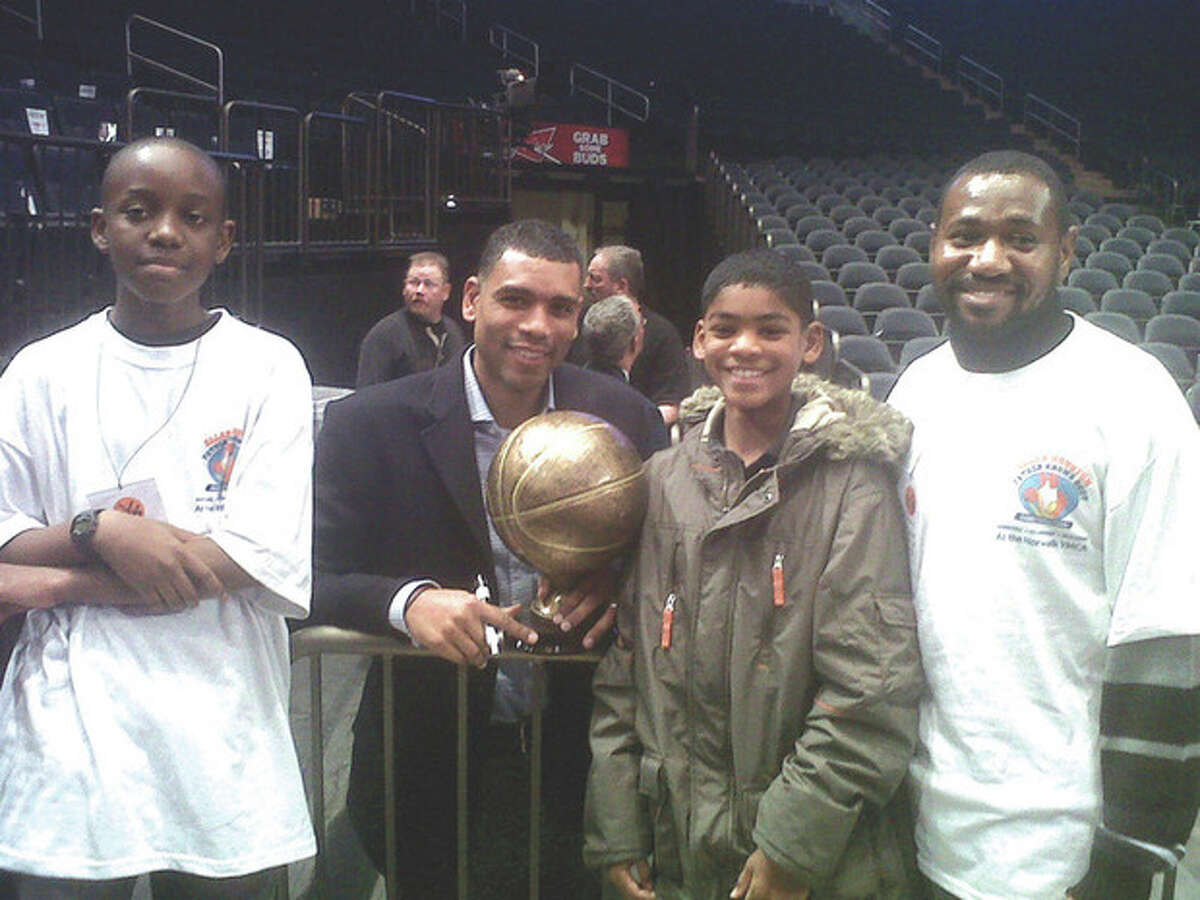 Contributed photo Geraine Anthony, far right, and his 11-year-old stepson, Jhani, far left, participate in New York Knicks star Allan Houston's father-child mentor program. Boy to right of Houston is his son, Allan Houston III.