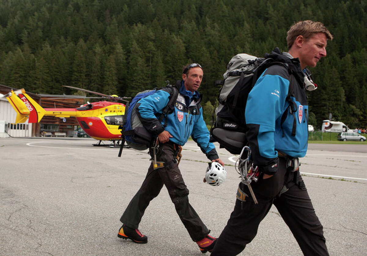 French rescue workers arrive at a helicopter landing area after an avalanche in the French Alps near Chamonix, France, swept at least nine climbers to their deaths, Thursday, July 12, 2012. About 28 climbers from Switzerland, Germany, Spain, France, Denmark and Serbia were believed to be involved in the expedition caught in the avalanche, according to the local gendarme service and Danish Foreign Ministry. (AP Photo/Anja Niedringhaus)