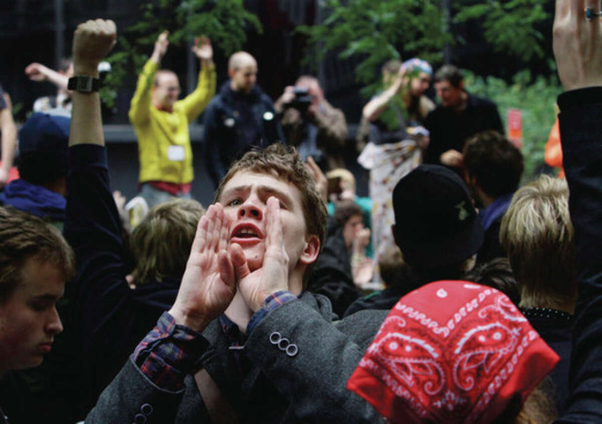 """Lucas Brinson, 21, from Davis, Calif, takes on the role of a human microphone, relaying information throughout Zuccotti Park's """"Occupy Wall Street"""" encampment on Thursday, Oct. 13, 2011 in New York. The owner of the private park where """"Occupy Wall Street"""" protesters have been camped out for nearly a month in lower Manhattan gave notice Thursday that it will begin enforcing regulations that prohibit everything from lying down on benches to storing personal property on the ground. The landlord, Brookfield Properties, handed out a notice to protesters saying they would be allowed back inside after a planned park cleanup on Friday morning if they abide by park regulations. (AP Photo/Bebeto Matthews)"""