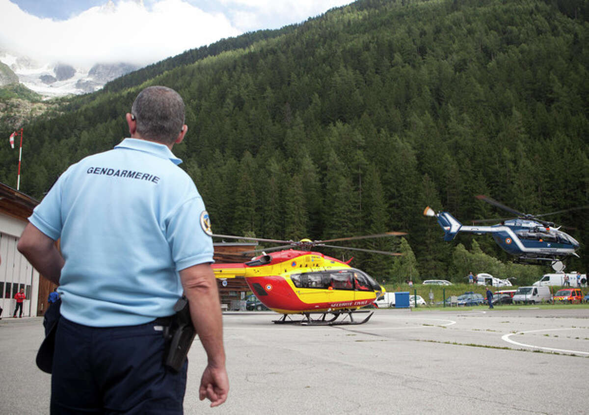 A French police officer observes the area as helicopters take off for a search mission after an avalanche in the French Alps near Chamonix, France, swept at least nine climbers to their deaths, Thursday, July 12, 2012. About 28 climbers from Switzerland, Germany, Spain, France, Denmark and Serbia were believed to be involved in the expedition caught in the avalanche, according to the local gendarme service and Danish Foreign Ministry. (AP Photo/Anja Niedringhaus)