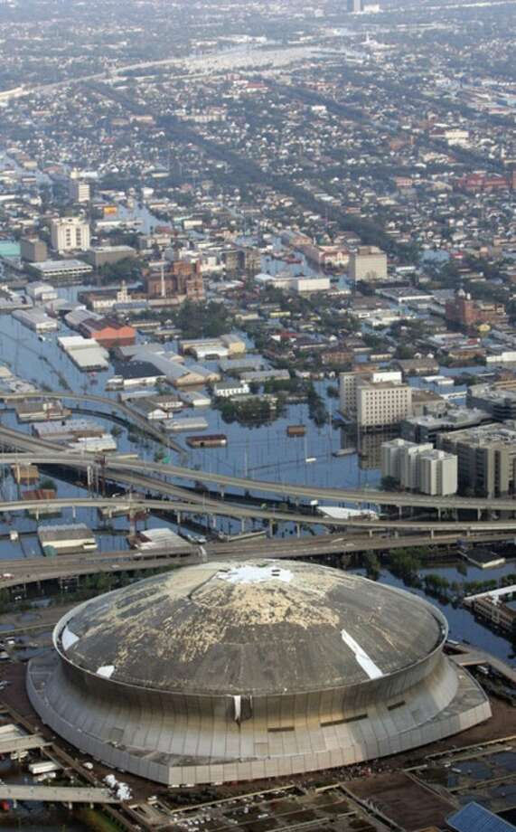 FILE - In this Aug. 30, 2005, file photo, The Louisiana Superdome is shown in this aerial view, which was damaged by Hurricane Katrina, surrounded by floodwaters, in New Orleans. Freakish weather, from this weekends October snowstorm to the long-lasting drought in the US Southwest, is striking more often. And global warming should make future weather even weirder, a special international report says. (AP Photo/David J. Phillip, File)