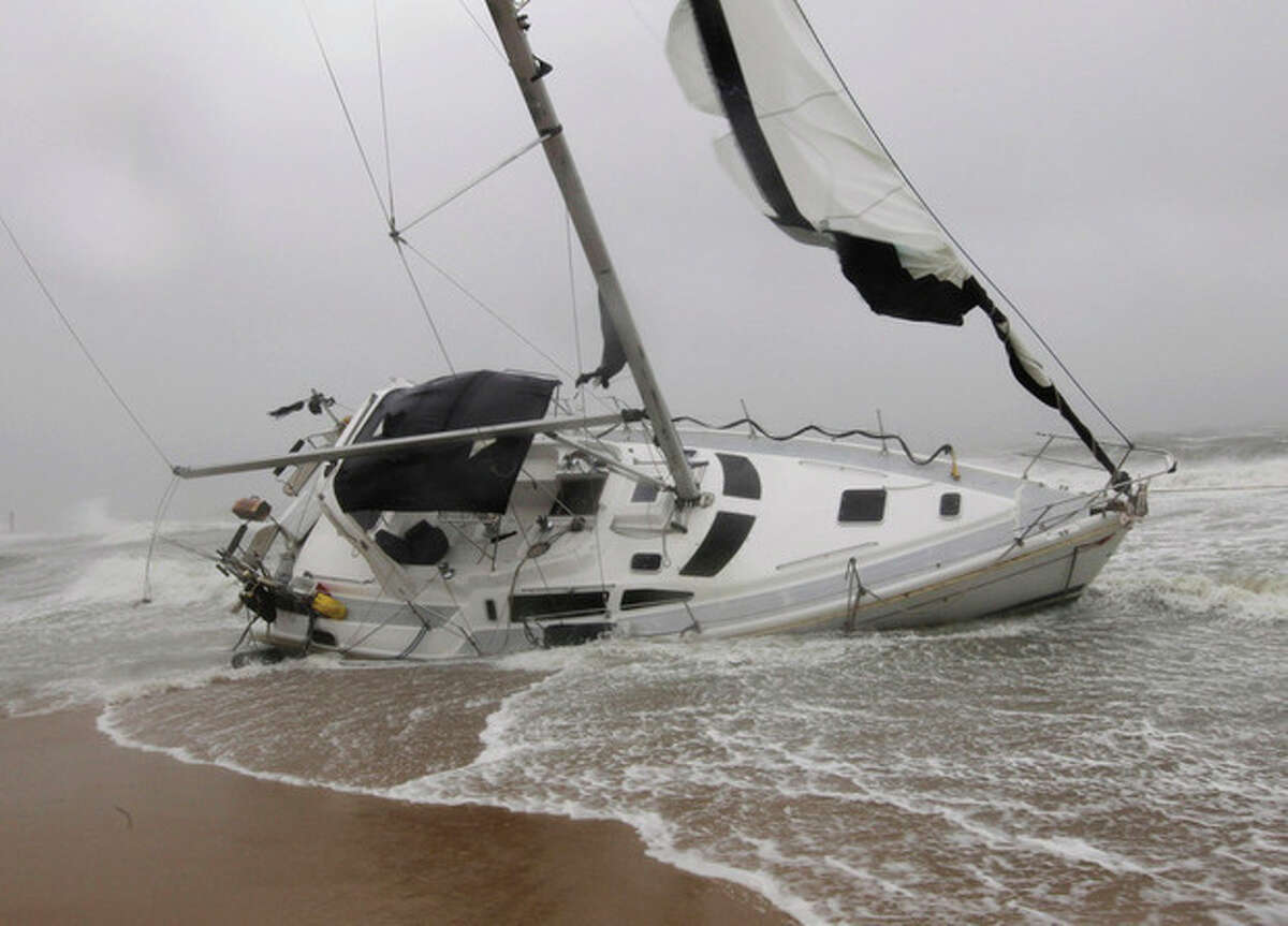 A stranded sailboat founders in the surf along the Willoughby Spit area of Norfolk, Va. as Hurricane Irene hits Norfolk, Va., Saturday, Aug. 27, 2011. They live aboard couple attempted to outrun the storm and got caught up in the high surf and wind. (AP Photo/Steve Helber)