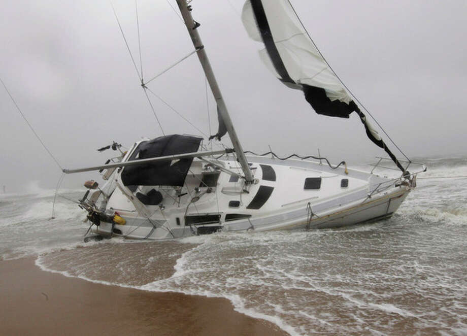 A stranded sailboat founders in the surf along the Willoughby Spit area of Norfolk, Va. as Hurricane Irene hits Norfolk, Va., Saturday, Aug. 27, 2011. They live aboard couple attempted to outrun the storm and got caught up in the high surf and wind. (AP Photo/Steve Helber) / AP