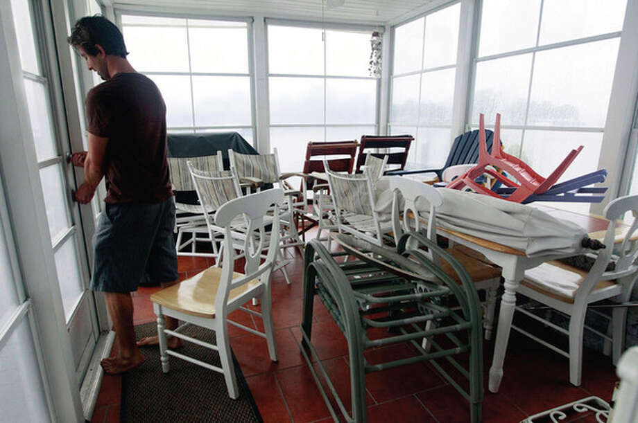 Keith Bondurant brings patio furniture inside to protect from high wind at his father's home in Ocean City, Md., Saturday, Aug. 27, 2011, as Hurricane Irene heads toward the Maryland coast. Officials in Ocean City say hundreds of residents have ignored mandatory evacuation orders ahead of Irene. (AP Photo/Patrick Semansky) / AP