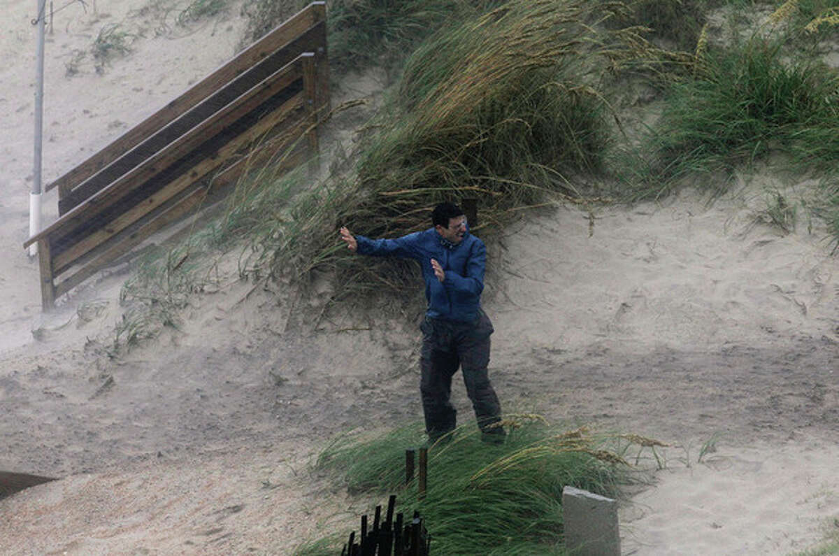 A man struggles against the wind while trying to walk over the dunes as the effects of Hurricane Irene are felt in Nags Head, N.C., Saturday, Aug. 27, 2011 (AP Photo/Gerry Broome)
