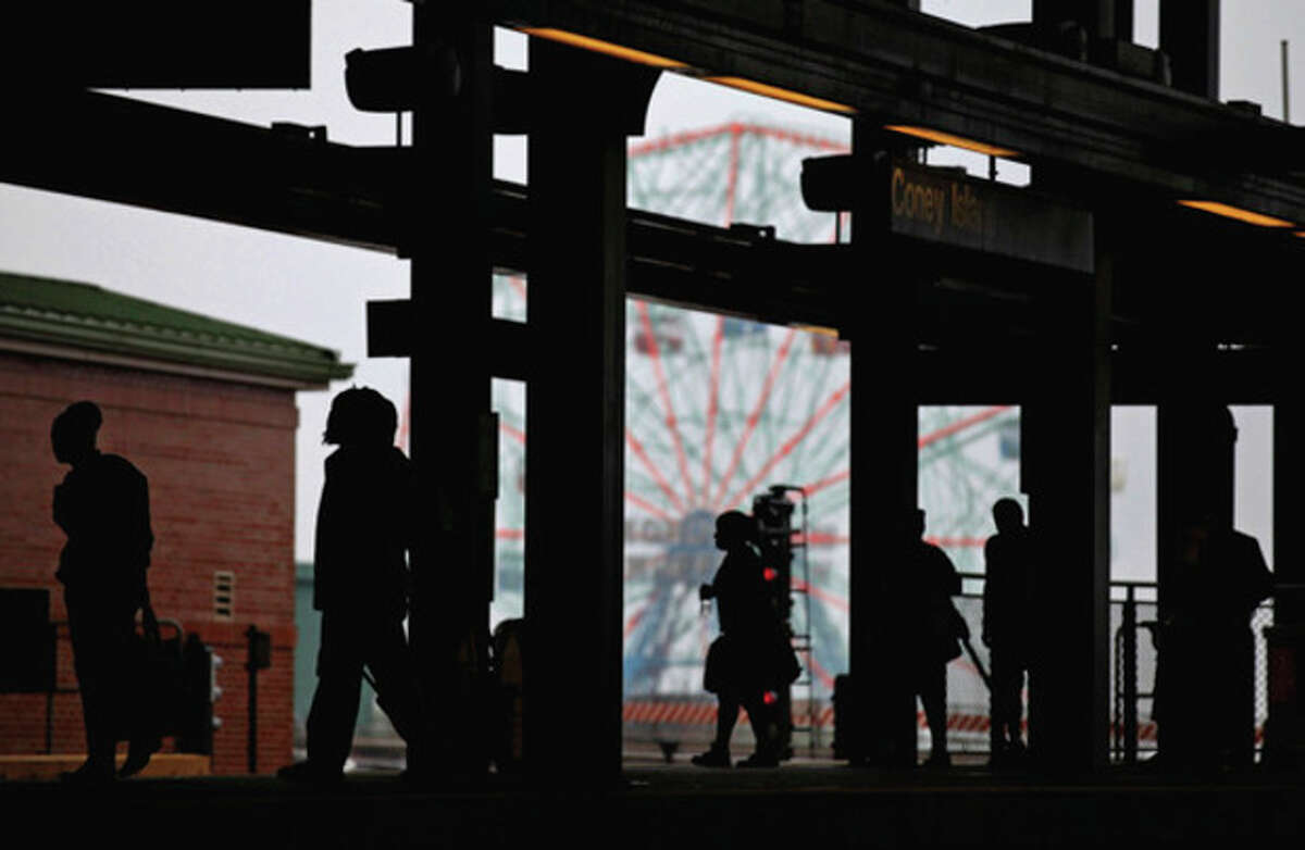 The Coney Island Wonder Wheel looms in the background as residents walks along the platform to catch one of the few remaining subway trains for the day while evacuating before the arrival of Hurricane Irene Saturday, Aug. 27, 2011 in Coney Island section of New York. (AP Photo/Craig Ruttle)