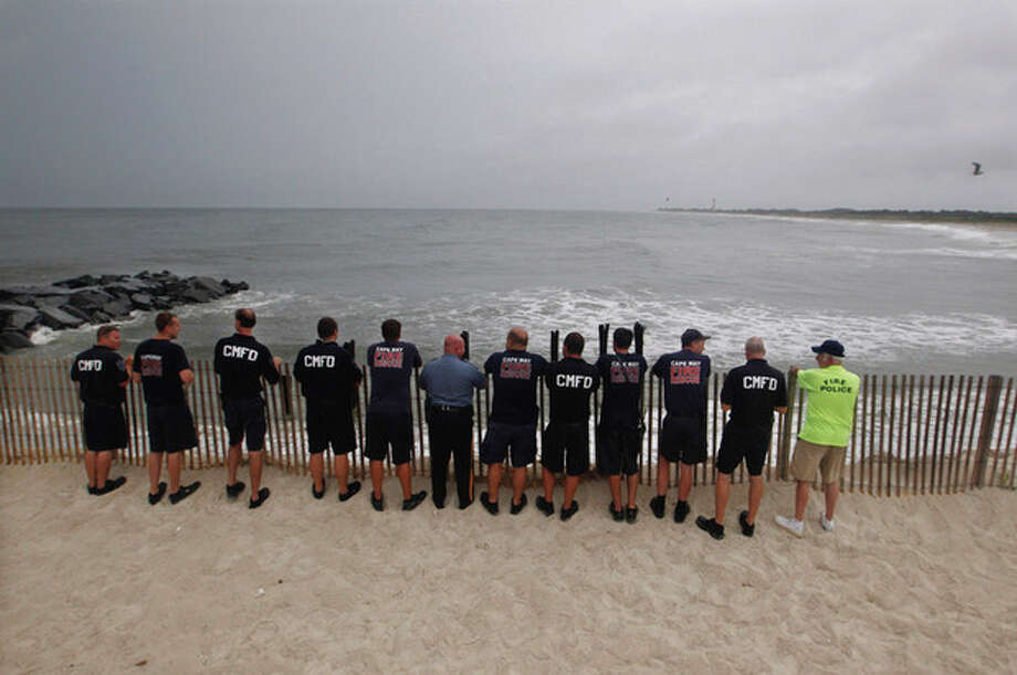 Members of Cape May Fire Department look look out at a stormy Atlantic early Saturday, Aug. 27, 2011, in Cape May, N.J. , as Hurricane Irene approaches. Hurricane-force winds and drenching rains from Irene battered the North Carolina coast early Saturday as the storm began its potentially catastrophic run up the Eastern Seaboard. (AP Photo/Mel Evans) / AP