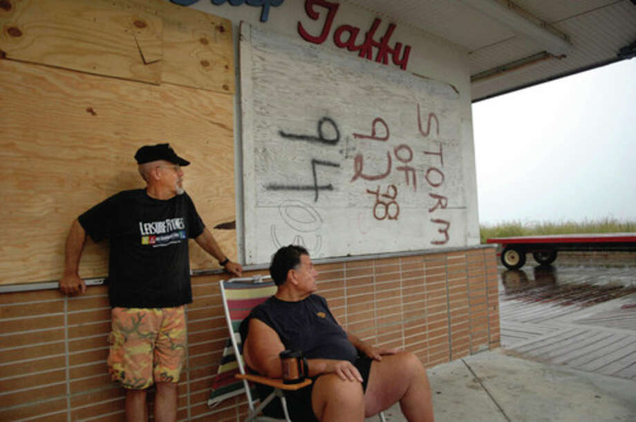 Locals Al Morris and Joe Dazio watch the approaching Hurricane Irene from Dolles in Rehoboth Beach early Saturday morning, Aug. 27, 2011 as a piece of plywood that has weathered many storms protects the business' windows. (AP Photo/The Daily Times, Chuck Snyder) / The Daily Times