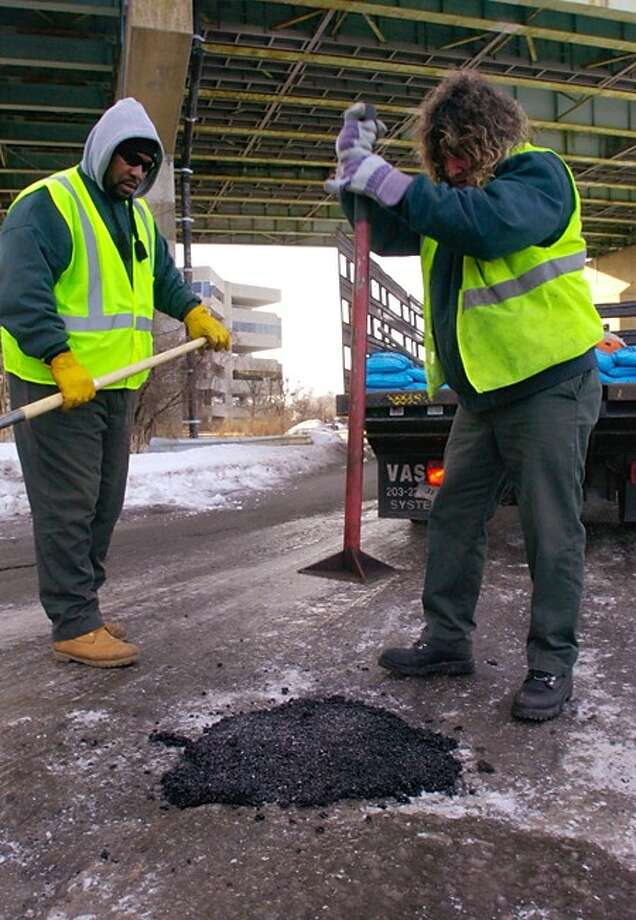 Norwalk Department of Public Works employees Chris Barnes and Brian Morrissey fill pot holes on Hendricks Ave. Hour photo / Erik Trautmann