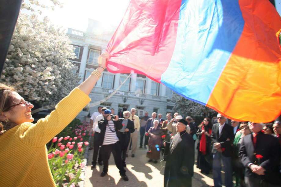 Sara Mushegian helps raise the Armenian flag in front of Greenwich Town Hall Friday morning during a program to commemorate the 95th anniversary of the Armenian Genocide. Photo: David Ames, David Ames/For Greenwich Time / Greenwich Time