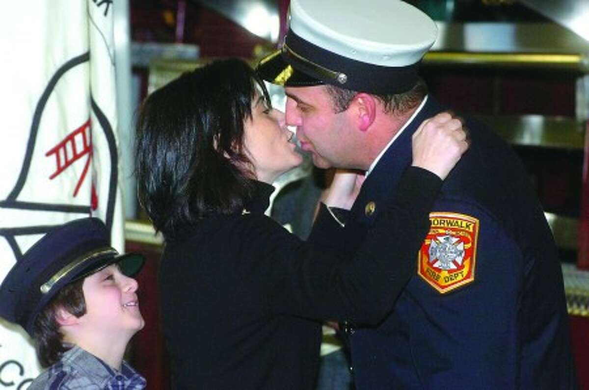 Photo/Alex von Kleydorff. Patricia Roos gives her husband Christoper Roos a kiss while 9yr old son Henry waits for a hug as he was promoted to Captain during a ceremony involving other Norwalk Fire Department promotions for Adam Tyrrell, Christian Hansen and Luca Feola.