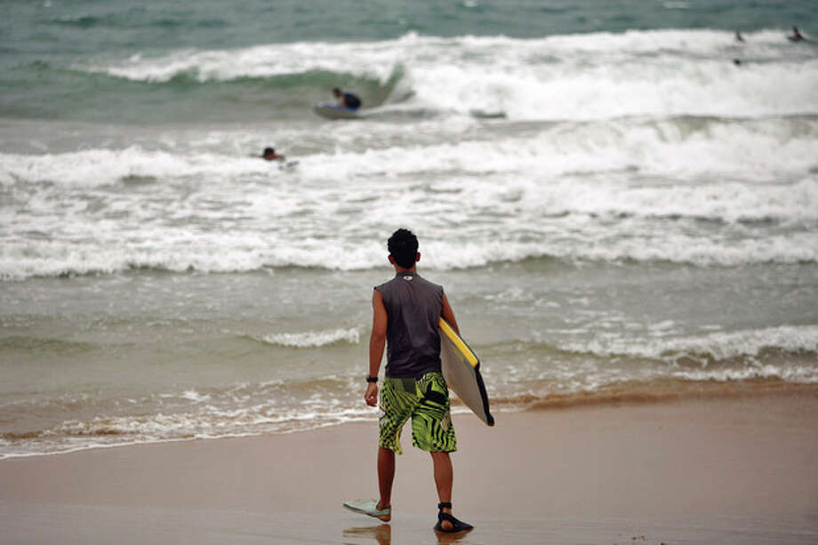 A surferÊwalks into the ocean asÊtropical stormÊIrene approaches to the island in Luquillo, Puerto Rico, Sunday, Aug. 21, 2011. The storm, packing winds of about 50 mph (85 kph) and tracking westward at 20 mph (32 kph), was expected to strengthen and pass near the U.S. island of Puerto Rico later Sunday or early Monday. (AP Photo/Ricardo Arduengo) / AP
