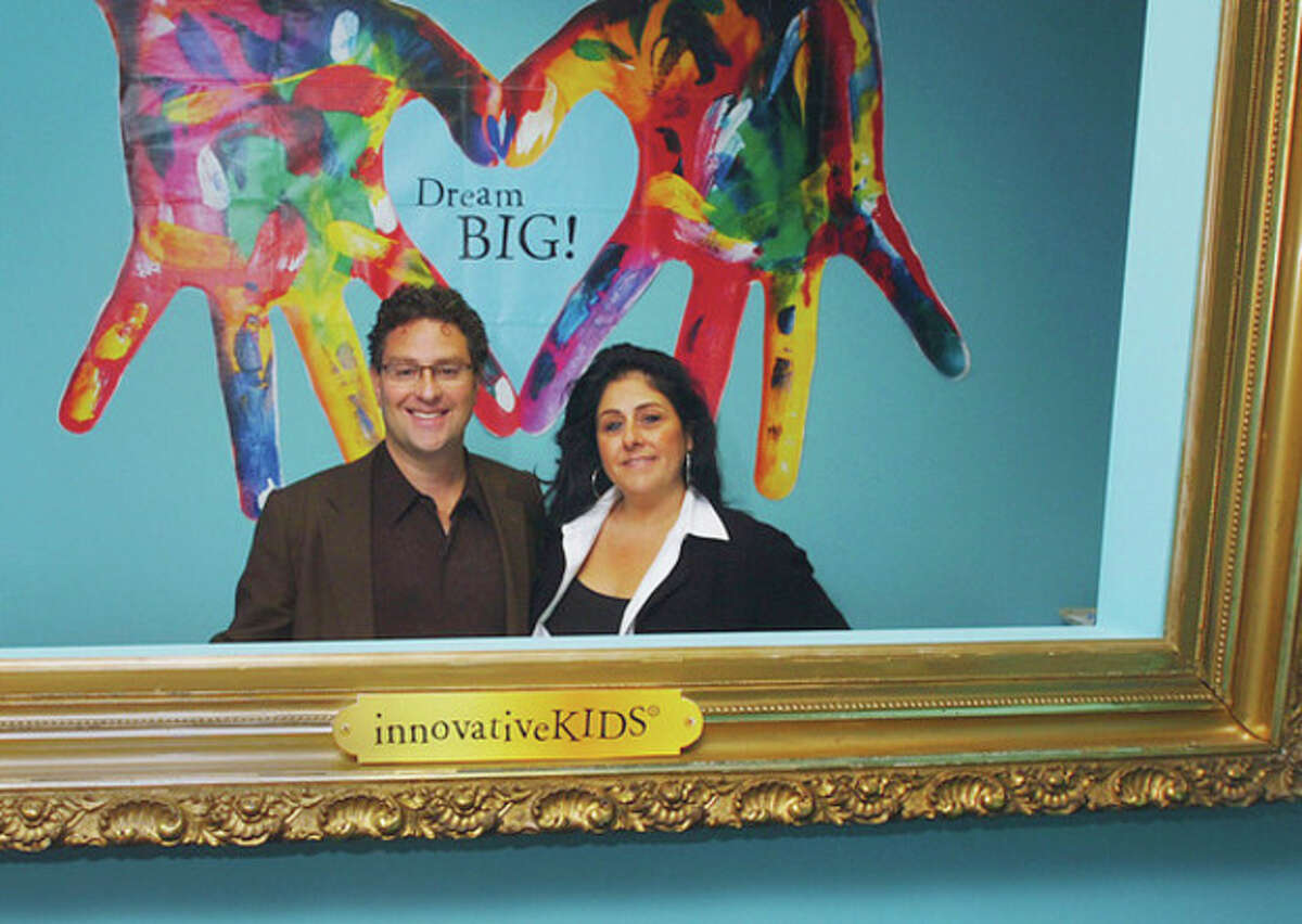 Hour photo / Erik Trautmann CEO Michael Levins and Shari Kaufman, president, of innovativeKids stand behind an open picture frame in the lobby of their new headquarters at 50 Washington Street.