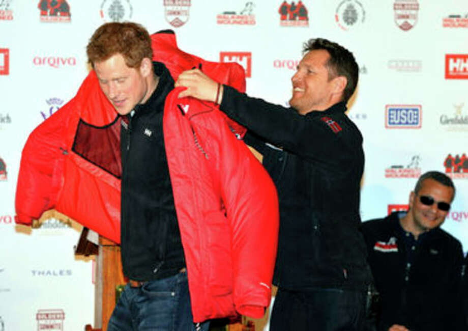 Prince Harry is presented with a red thermal coat during the launch event of the Walking With The Wounded South Pole Allied Challenge 2013 at the Mandarin Oriental Hotel, London, Friday April 19, 2013. Prince Harry will take part in a race to the South Pole with a team of wounded British servicemen and women, he announced today. The 28-year-old will take on teams from the United States and the Commonwealth in the 208-mile (335km) Walking With The Wounded South Pole Allied Challenge in November and December this year.(AP Photo, PA, John Stillwell) UNITED KINGDOM OUT NO ARCHIVE NO SALES / PA