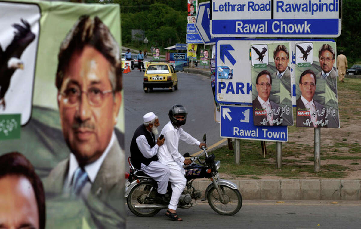 Pakistani men ride a motorcycle past posters showing former President and military ruler Pervez Musharraf, in Islamabad, Pakistan, Friday, April 19, 2013. Police arrested Musharraf overnight at his home in the capital, where he had holed up following a dramatic escape from court to avoid being detained, officials said Friday. (AP Photo/Muhammed Muheisen)