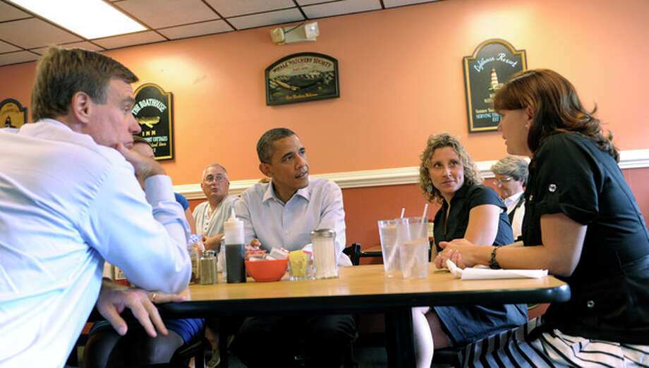President Barack Obama, accompanied by and Sen. Mark Warner, D-Va., left, talks with Cari Beauregard, right, and Jennifer Farlin, second from right, at Rick's Cafe in Virginia Beach, Va., Friday, July 13, 2012. The women are all military spouses from Chesapeake, Va. Obama is spending the day in Virginia campaigning. (AP Photo/Susan Walsh) / AP