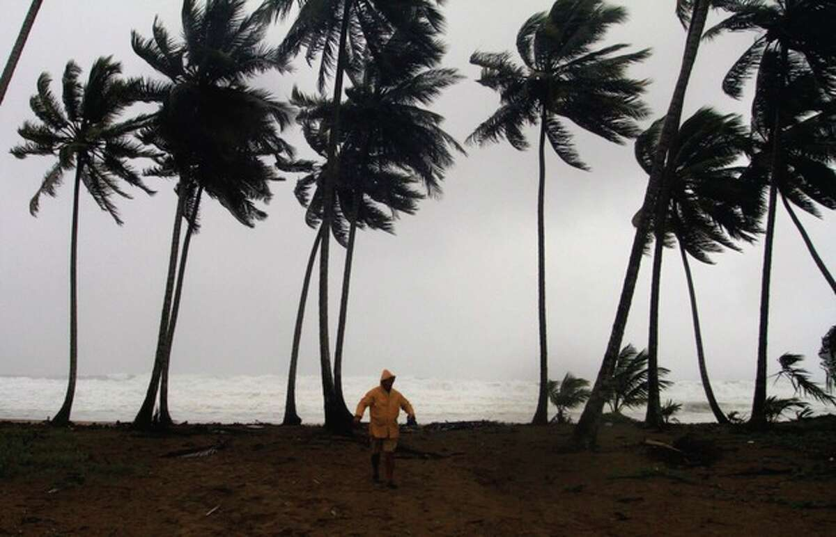 A man walks away from Los Yayales beach after watching the sea surge due to the approach of Hurricane Irene to Nagua, in the northern coast of the Dominican Republic, Monday, Aug, 22, 2011. A strengthening Category 2 Hurricane Irene roared off the Dominican Republic's resort-dotted northern coast on Monday night, whipping up high waves and torrential downpours on a track that could slam it into the U.S. Southeast as a major storm by the end of the week. (AP Photo/Roberto Guzman)