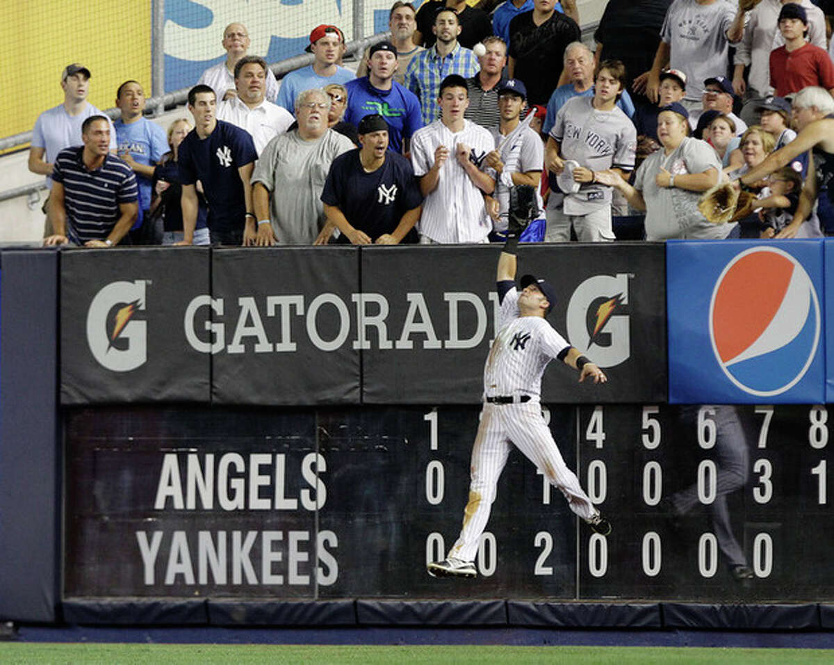 New York Yankees' Nick Swisher catches a ball hit by Los Angeles Angels' Mark Trumbo during the eighth inning of a baseball game, Friday, July 13, 2012, in New York. (AP Photo/Frank Franklin II)