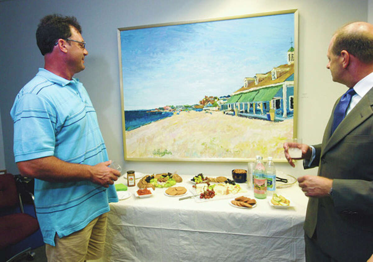 Hour photo / Erik Trautmann Artist Jim Chillington and chairman of the Norwalk Arts Commission, Emil Albanese, look over Chillington's work during the opening reception of the Mayor's Gallery Thursday outside the mayor's office.