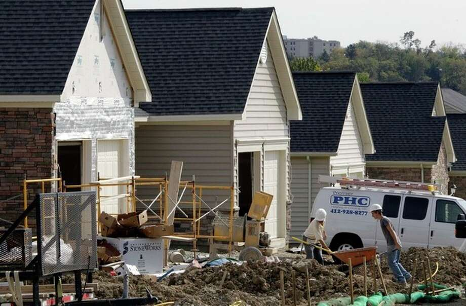 Construction workers build new homes in Bridgeville, Pa., Monday, Oct. 18, 2011. Builders broke ground on more homes in September, but permits for future construction fell, a grim sign for the housing market. (AP Photo/Gene J. Puskar) / AP