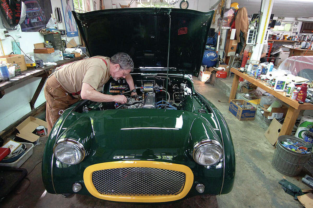 Photo by Alex von Kleydorff. Kevin Craw works on setting the right tension on a throttle spring in his 1962 Triumph TR3, one of the cars on display at the Wilton Kiwanis car show July 15.