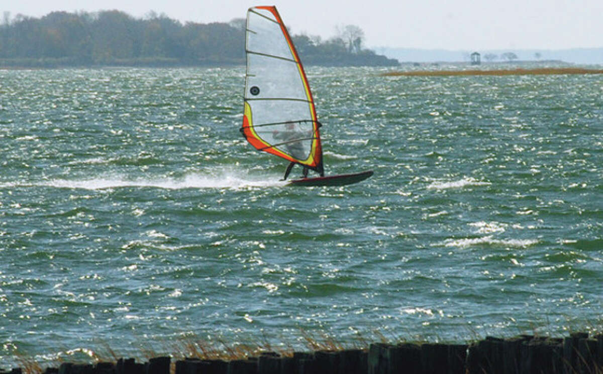 A windsurfer takes advantage of the windy conditions Saturday on the waters off Calf Pasture Beach. Hour photo / Erik Trautmann