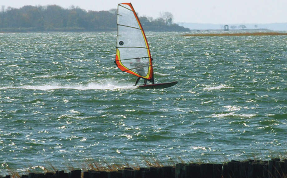 A windsurfer takes advantage of the windy conditions Saturday on the waters off Calf Pasture Beach. Hour photo / Erik Trautmann / (C)2011, The Hour Newspapers, all rights reserved