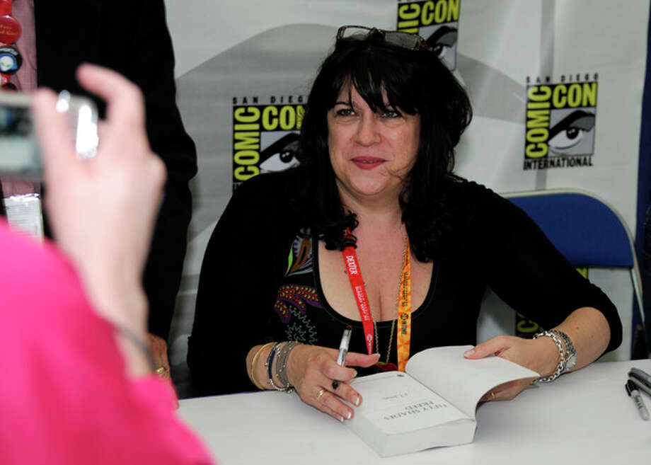 "Author E.L. James signs a copy of her book ""Fifty Shades of Grey"" during the first day of Comic-Con convention held at the San Diego Convention Center on Thursday July 12, 2012, in San Diego. (Photo by Denis Poroy/Invision/AP) / 2012 Invision"