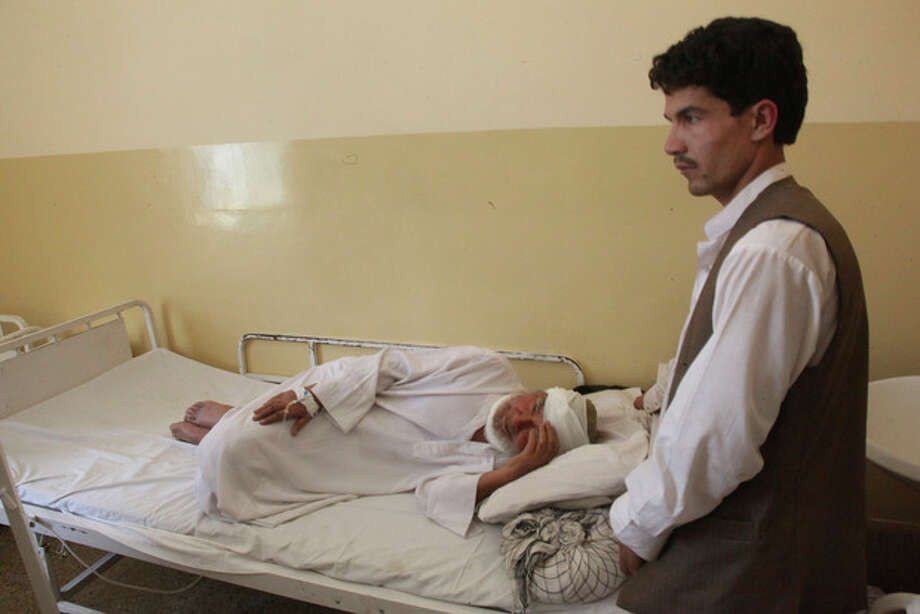 An Afghan man who was wounded in a suicide attack lies in a hospital in Samangan province north of Kabul Afghanistan, Saturday, July, 14, 2012. A suicide bomber blew himself up Saturday in a wedding hall in northern Afghanistan, killing at least 23 people including a prominent warlord-turned-politician and three Afghan security force officials, in an attack that deals a setback to efforts to unify the nation's ethnic factions, Afghan officials said. (AP Photo/Jawed Dehsabzi) / AP