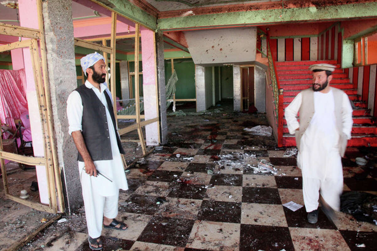 Afghan men inspect a damaged wedding hall that was the site of a bombing in Samangan province, north of Kabul, Afghanistan, Saturday, July, 14, 2012. A suicide bomber blew himself up Saturday in a wedding hall in northern Afghanistan, killing at least 23 people including a prominent warlord-turned-politician and three Afghan security force officials, in an attack that deals a setback to efforts to unify the nation's ethnic factions, Afghan officials said. (AP Photo/Jawed Dehsabzi)