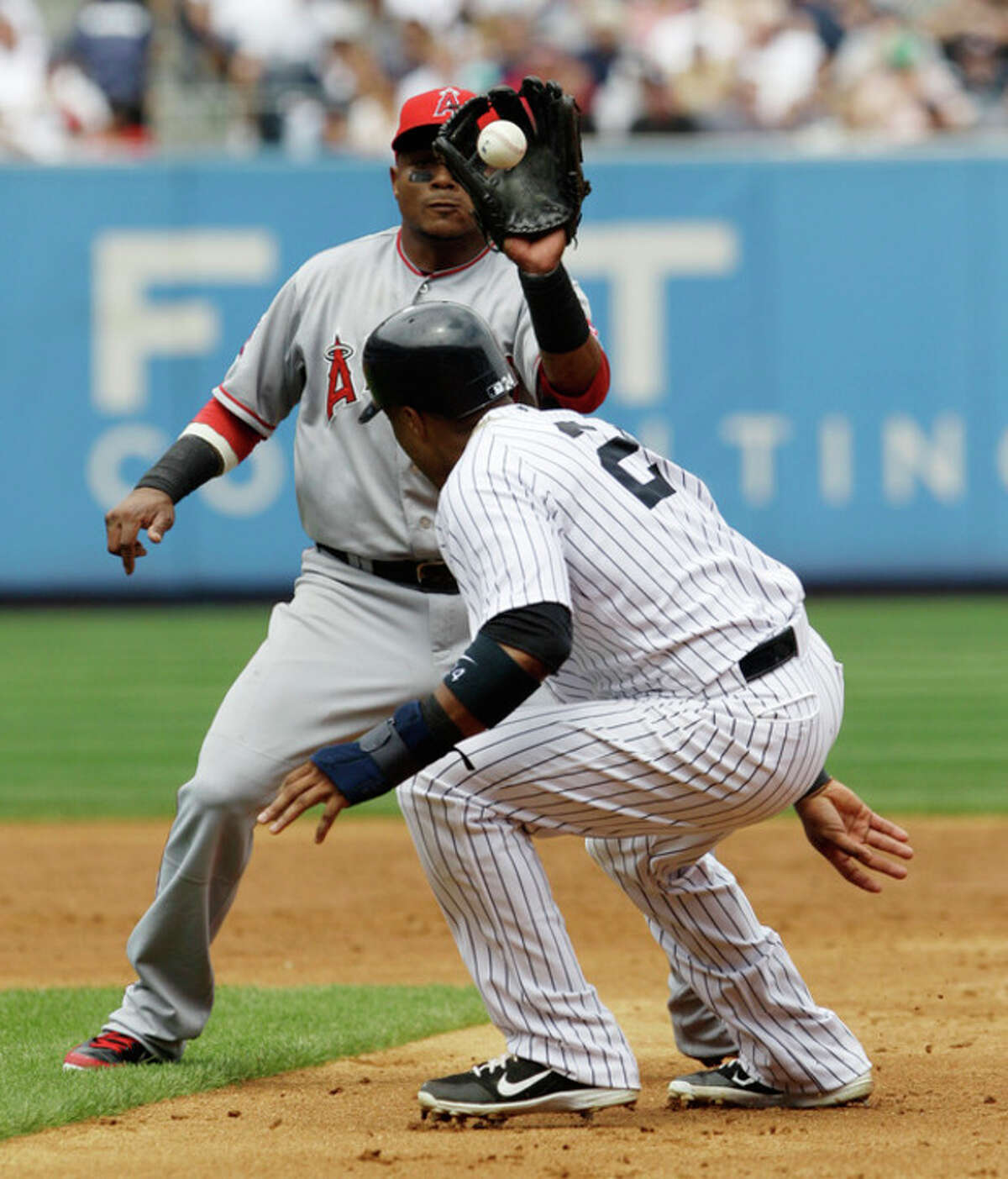 Los Angeles Angels shortstop Erick Aybar has the throw in his glove as he catches New York Yankees Robinson Cano in a third-inning rundown during their baseball game at Yankee Stadium in New York, Sunday, July 15, 2012. (AP Photo/Kathy Willens)