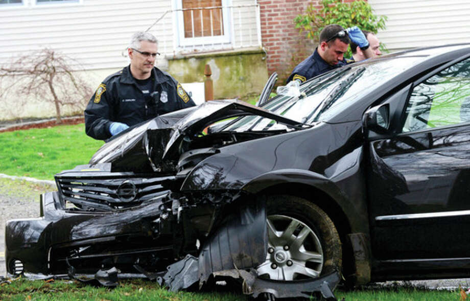 Norwalk police chased a driver in a black Nissan through the Dry Hill neighborhood where he crashed into a tree Saturday.Hour photo / Erik Trautmann / (C)2013, The Hour Newspapers, all rights reserved