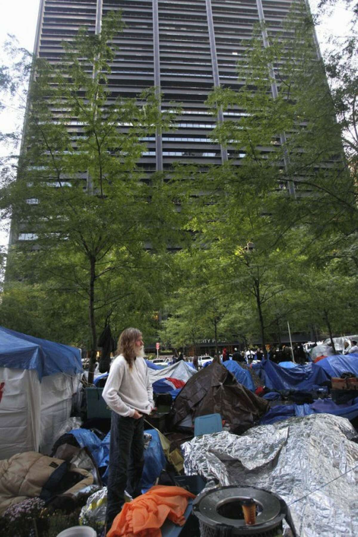 """FILE - In this Oct. 20, 2011 file photo, an Occupy Wall Street protester stands amid tarps and sleeping bags while a building owned by Brookfield Properties towers over Zuccotti Park in New York. Most Americans say politics makes them angry. But that doesn't mean there is wide support for the Wall Street protests against the nation's power brokers. The latest Associated Press-GfK poll shows that 37 percent of people do back the protests that have spread from New York to cities across the country. It's one of the first snapshots of how the public views the """"Occupy Wall Street"""" movement. (AP Photo/Seth Wenig, File)"""
