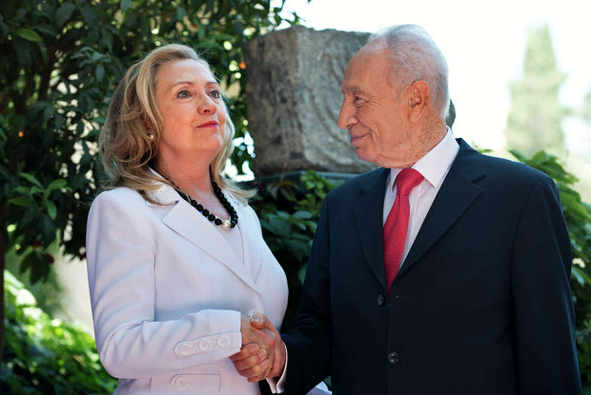Israel's President Shimon Peres, right, and U.S. Secretary of State Hillary Rodham Clinton, left, shake hands before their meeting at the President's residence in Jerusalem, Monday, July 16, 2012. Although Clinton's agenda is designed to cover the breadth of U.S.-Israeli relations, the lack of action on peace talks between Israel and the Palestinians will be in the spotlight. (AP Photo/ Brendan Smialowski, Pool)