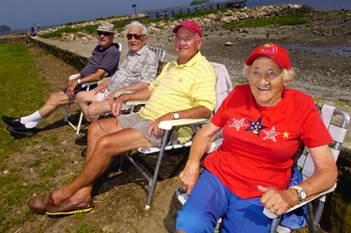George Smith, Joe Wesloski, Karl Teigland and Nancy Teigland stake out their spots at Calf Pasture Beach for the Memorial Day weekend early Friday. Hour photo / Erik Trautmann