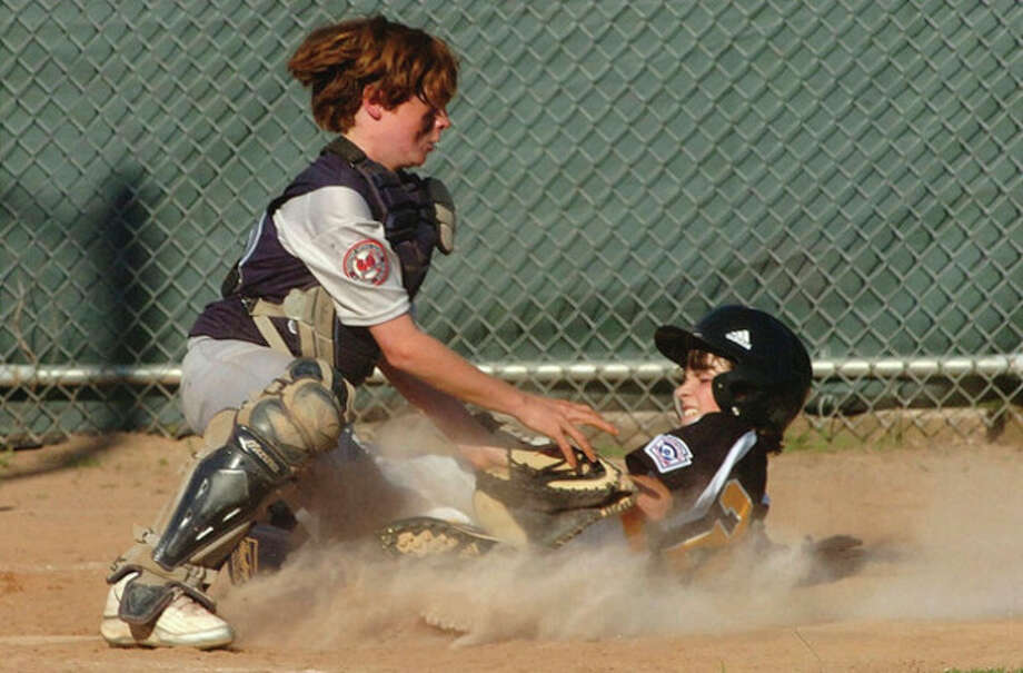 Hour photo/Alex von Kleydorff Westport catcher Julian Ross blocks the plate and tries to corral a loose ball as Trumbull AmericanÕs S.J. Arnone slides home during TuesdayÕs Little League District 2 encounter in Bridgeport. Westport stayed alive with a 10-3 victory in the losers bracket clash. / 2011 The Hour Newspapers