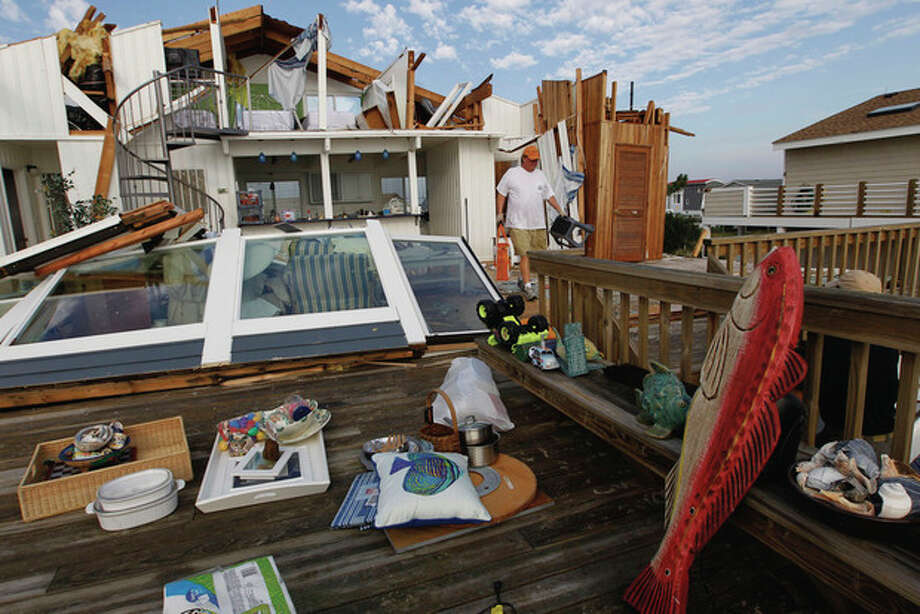 Casey Robinson clears out belongings from his severely storm-damaged beach home in the Sandbridge area of Virginia Beach, Va., after Hurricane Irene hit the region, Sunday, Aug. 28, 2011. Irene inflicted scattered damage over such a broad area that the total damage _ and costs involved _ were not yet known. (AP Photo/Steve Helber) / AP
