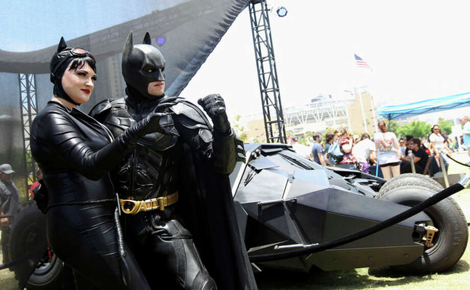 """Comic-Con attendees Katie Mitchell, left, and Jonathan Graves, from Los Angeles, strike a pose in front of the Tumbler Batmobile """"Batman Begins"""" and """"The Dark Knight"""" during Comic-Con, Saturday, July 14, 2012, in San Diego. (Photo by Matt Sayles/Invision/AP) / 2012 Invision"""