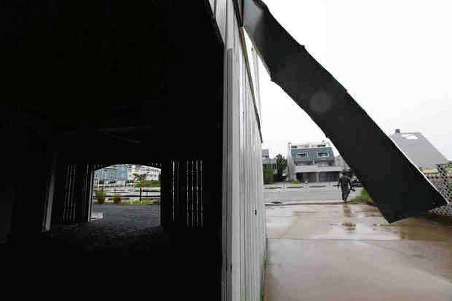 A man walks near damage to a home from Hurricane Irene along the boardwalk of Bethany Beach, Del. (AP Photo/The Wilmington News-Journal, Suchat Pederson) / The News Journal-2011