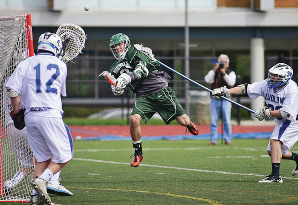 Hour photo/Erik Trautmann Norwalk's Sean Largay goes airborne as he fires a shot on goal during Saturday's game at Fairfield Ludlowe. The Falcons pulled away from the visiting Bears to score an 11-5 victory.