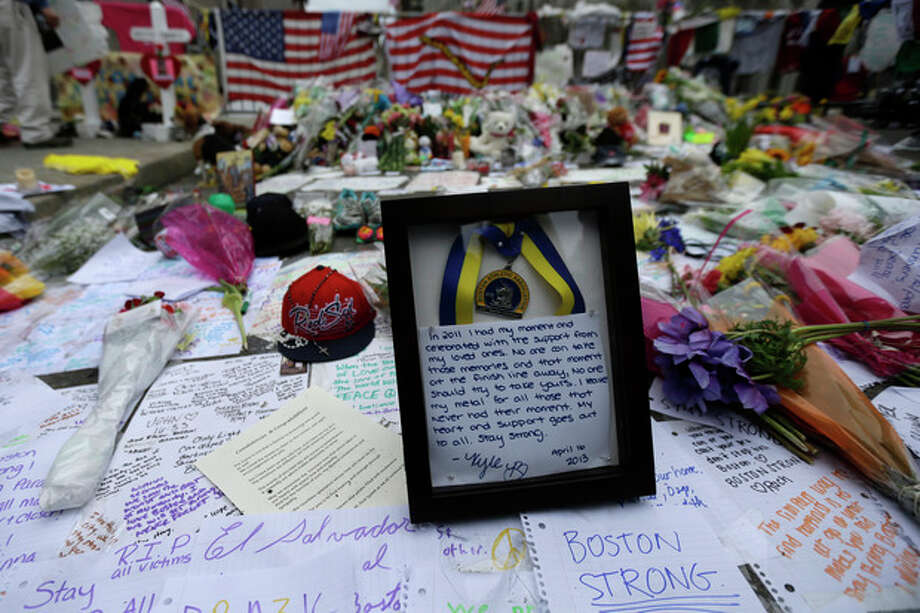 Shown are items left at a makeshift memorial near the finish line of Monday's Boston Marathon explosions, which killed at least three and injured more than 140, Thursday, April 18, 2013, in Boston. (AP Photo/Matt Rourke) / AP