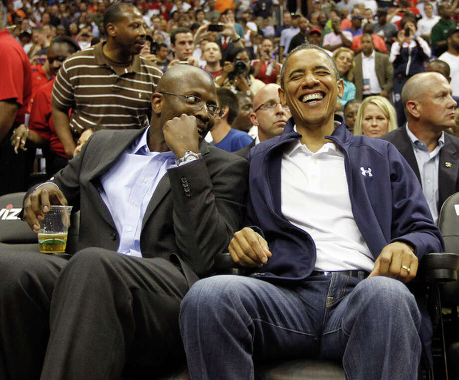 President Barack Obama, right, smiles as he talks with his former special assistant and personal aide Reggie Love, left, as they attend an Olympic men's exhibition basketball game with Brazil and Team USA in Washington, Monday, July 16, 2012. (AP Photo/Pablo Martinez Monsivais) / AP2012