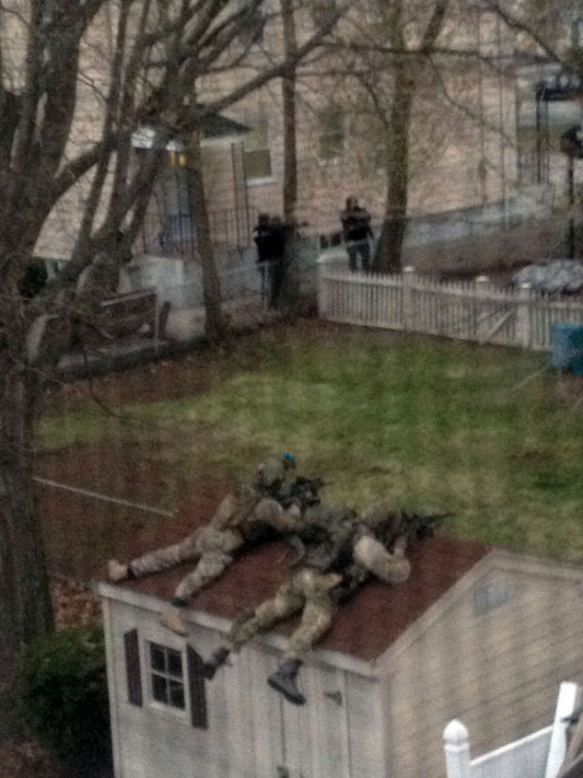This photo shot through a window screen provided by Samantha England, shows police in tactical gear outside England's home in Watertown, Mass. Friday, April 19, 2013. The two suspects in the Boston Marathon bombing killed an MIT police officer and hurled explosives at police in a car chase and gun battle overnight that left one of them dead and his brother on the loose, authorities said Friday as thousands of officers swarmed the streets in a manhunt that all but paralyzed the Boston area. (AP Photo/Samantha England)