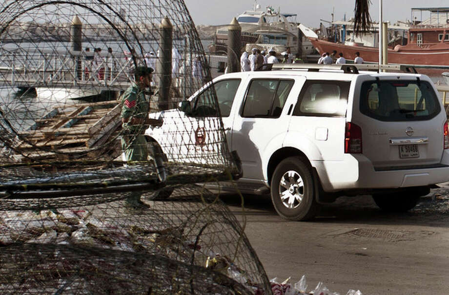 Emirati police and other officials inspect a boat docked in a fishing harbor in the Jumeirah district of Dubai, United Arab Emirates, Monday, July 16, 2012. A U.S. official in Dubai says an American vessel has fired on a boat off the coast of the United Arab Emirates, killing one person and injuring three. The official gave no further details, but it appears the boat could have been mistaken as a threat in Gulf waters not far from Iran's maritime boundaries. (AP Photo/Almoutasim Almaskery) / AP
